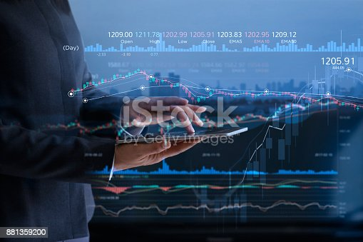 istock Business people checking stock market on tablet and analysing financial data on a screen with graph and candlestick chart on LED monitor virtual on the city background 881359200