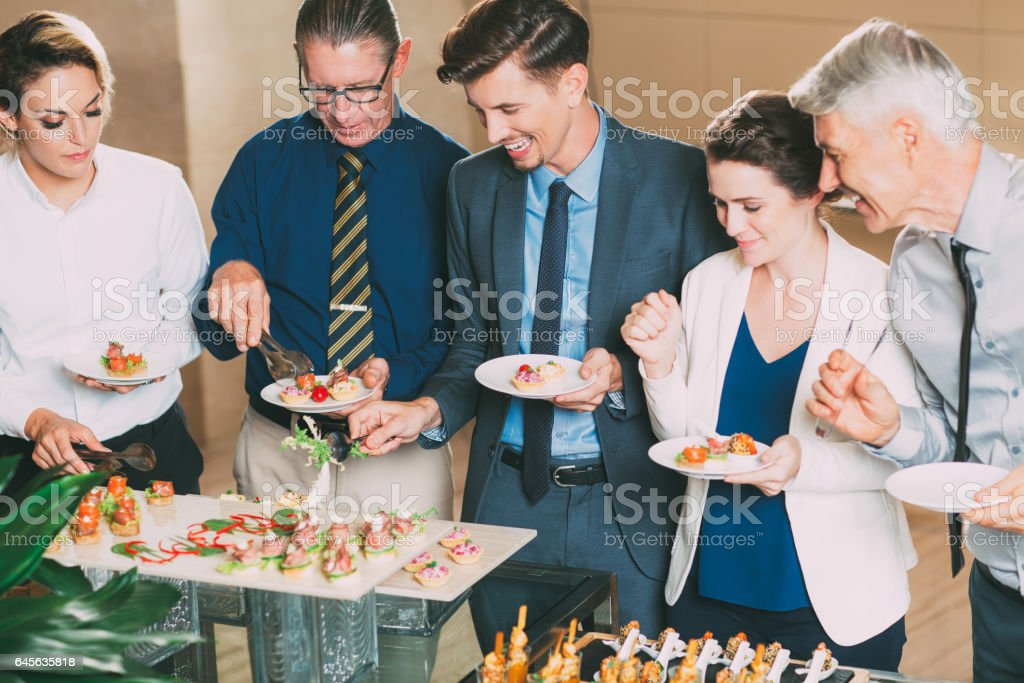 Business People Choosing Snacks at Buffet Table stock photo