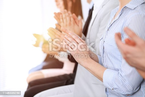 1153898364 istock photo Business people clapping and applause at meeting or conference, close-up of hands. Group of unknown businessmen and women in modern white office. Success teamwork or corporate coaching concept 1148335230