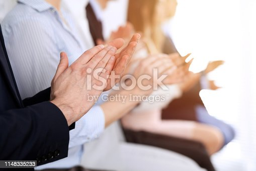 1153898364 istock photo Business people clapping and applause at meeting or conference, close-up of hands. Group of unknown businessmen and women in modern white office. Success teamwork or corporate coaching concept 1148335233