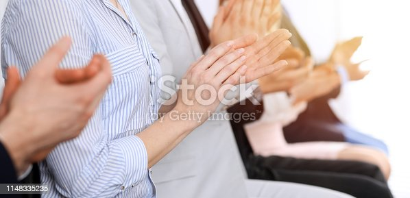 1153898364 istock photo Business people clapping and applause at meeting or conference, close-up of hands. Group of unknown businessmen and women in modern white office. Success teamwork or corporate coaching concept 1148335235
