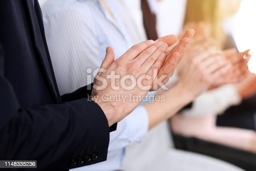 1153898364 istock photo Business people clapping and applause at meeting or conference, close-up of hands. Group of unknown businessmen and women in modern white office. Success teamwork or corporate coaching concept 1148335236