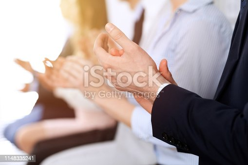 1153898364 istock photo Business people clapping and applause at meeting or conference, close-up of hands. Group of unknown businessmen and women in modern white office. Success teamwork or corporate coaching concept 1148335241