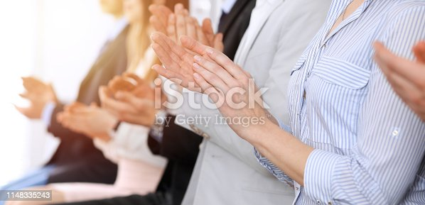 1153898364 istock photo Business people clapping and applause at meeting or conference, close-up of hands. Group of unknown businessmen and women in modern white office. Success teamwork or corporate coaching concept 1148335243