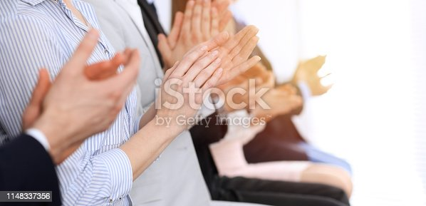 1153898364 istock photo Business people clapping and applause at meeting or conference, close-up of hands. Group of unknown businessmen and women in modern white office. Success teamwork or corporate coaching concept 1148337356