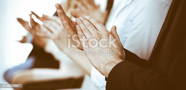 1153898364 istock photo Business people clapping and applause at meeting or conference, close-up of hands. Group of unknown businessmen and women in modern white office. Success teamwork or corporate coaching concept 1148338621