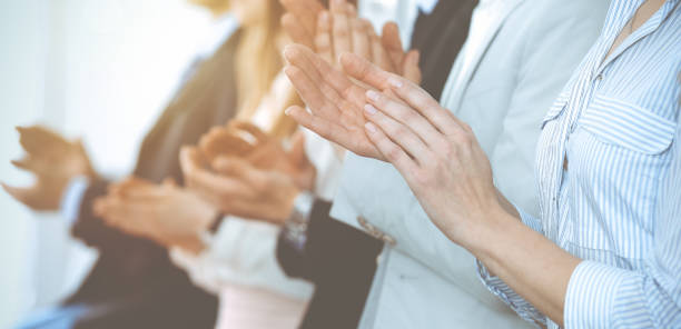 business people clapping and applause at meeting or conference, close-up of hands. group of unknown businessmen and women in modern white office. success teamwork or corporate coaching concept - applaudire foto e immagini stock