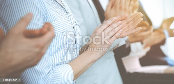 1153898364 istock photo Business people clapping and applause at meeting or conference, close-up of hands. Group of unknown businessmen and women in modern white office. Success teamwork or corporate coaching concept 1153899218