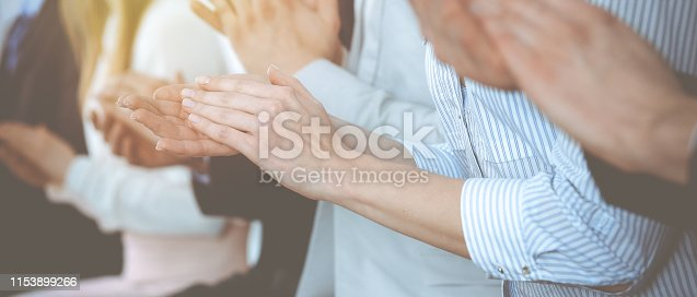 1153898364 istock photo Business people clapping and applause at meeting or conference, close-up of hands. Group of unknown businessmen and women in modern white office. Success teamwork or corporate coaching concept 1153899266