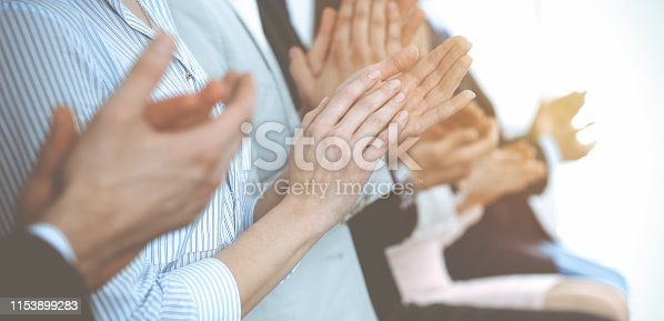 1153898364 istock photo Business people clapping and applause at meeting or conference, close-up of hands. Group of unknown businessmen and women in modern white office. Success teamwork or corporate coaching concept 1153899283