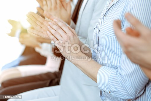 1153898364 istock photo Business people clapping and applause at meeting or conference, close-up of hands. Group of unknown businessmen and women in modern white office. Success teamwork or corporate coaching concept. 1158602778