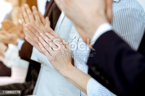1153898364 istock photo Business people clapping and applause at meeting or conference, close-up of hands. Group of unknown businessmen and women in modern white office. Success teamwork or corporate coaching concept. 1158602779