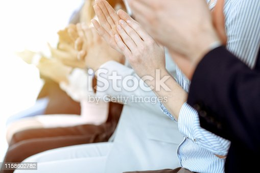 1153898364 istock photo Business people clapping and applause at meeting or conference, close-up of hands. Group of unknown businessmen and women in modern white office. Success teamwork or corporate coaching concept. 1158602782