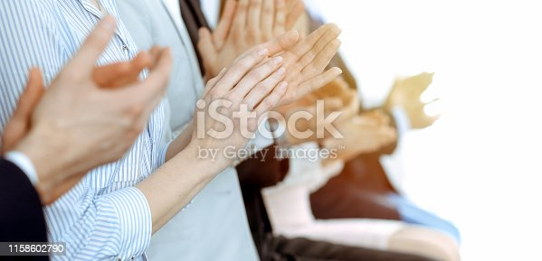 1153898364 istock photo Business people clapping and applause at meeting or conference, close-up of hands. Group of unknown businessmen and women in modern white office. Success teamwork or corporate coaching concept. 1158602790