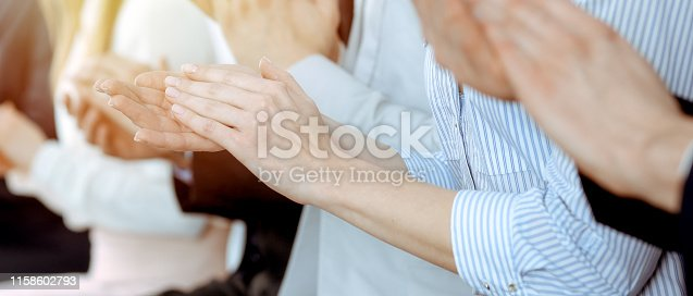 1153898364 istock photo Business people clapping and applause at meeting or conference, close-up of hands. Group of unknown businessmen and women in modern white office. Success teamwork or corporate coaching concept. 1158602793