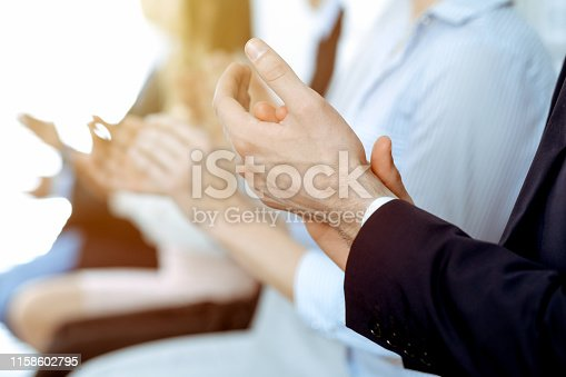 1153898364 istock photo Business people clapping and applause at meeting or conference, close-up of hands. Group of unknown businessmen and women in modern white office. Success teamwork or corporate coaching concept. 1158602795