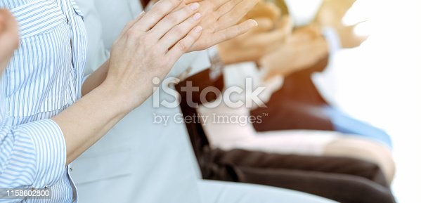 1153898364 istock photo Business people clapping and applause at meeting or conference, close-up of hands. Group of unknown businessmen and women in modern white office. Success teamwork or corporate coaching concept. 1158602800