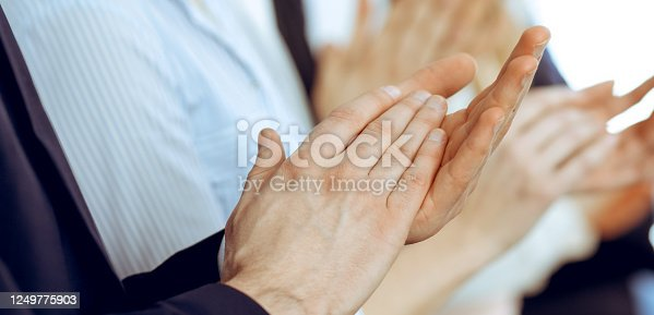 1153898364 istock photo Business people clapping and applause at meeting or conference, close-up of hands. Group of unknown businessmen and women in modern white office. Success teamwork or corporate coaching concept 1249775903