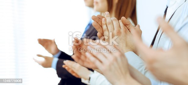 1153898364 istock photo Business people clapping and applause at meeting or conference, close-up of hands. Group of unknown businessmen and women in modern white office. Success teamwork or corporate coaching concept 1249775906