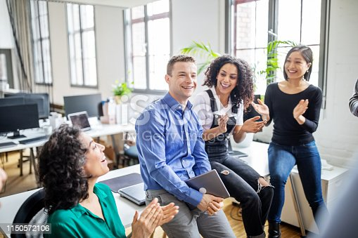 istock Business people clapping for male colleague in office 1150572106