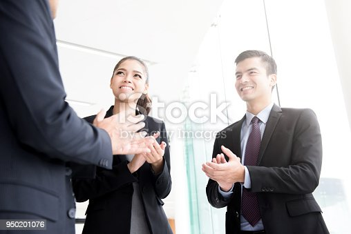 878220300 istock photo Business people  clapping their hands at building corridor 950201076