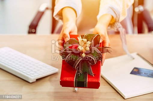 918365170 istock photo Business people closeup hand giving present gift box in office party celebration event. 1194434221