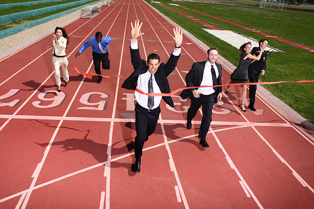 business people crossing finish line - finishing stock photos and pictures