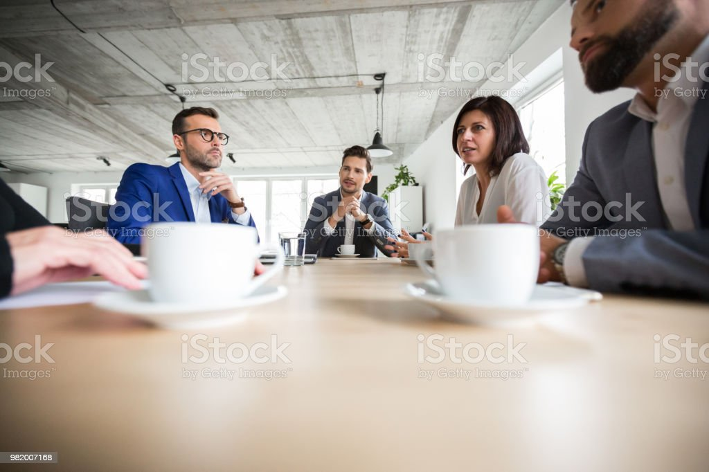 Business people discussing about project in boardroom Group of business people working together in office. Business people discussing about project in boardroom. Adult Stock Photo
