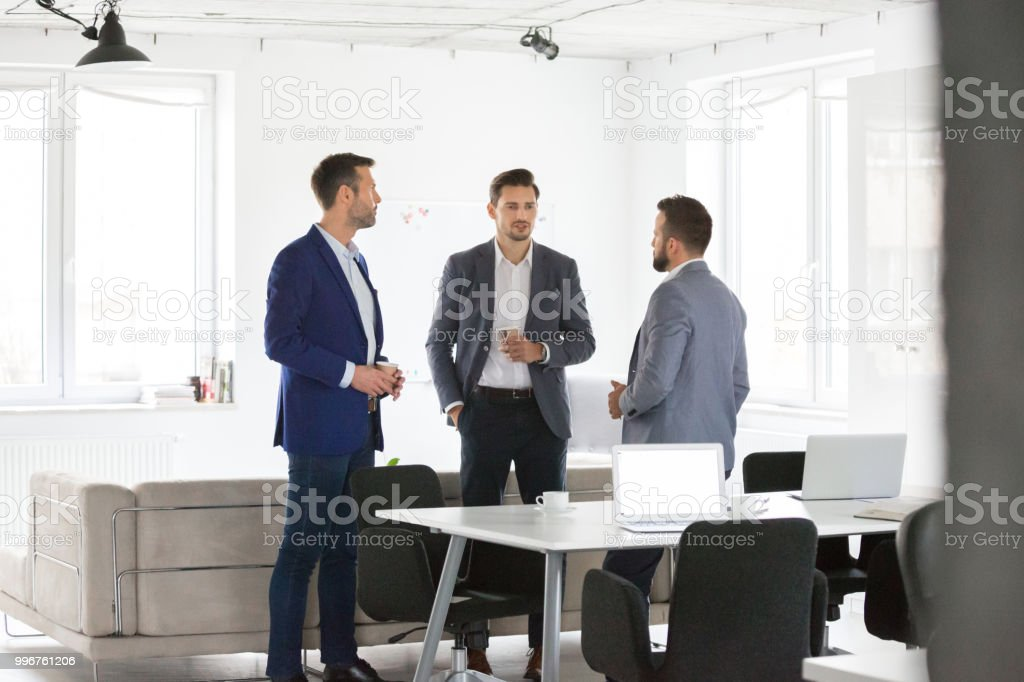 Business people discussing at coffee break Three businessmen discussing during coffee break in office. Group of business people talking during a break in office. Adult Stock Photo