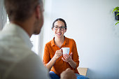 Happy  woman discussing with male colleague during coffee break at office.