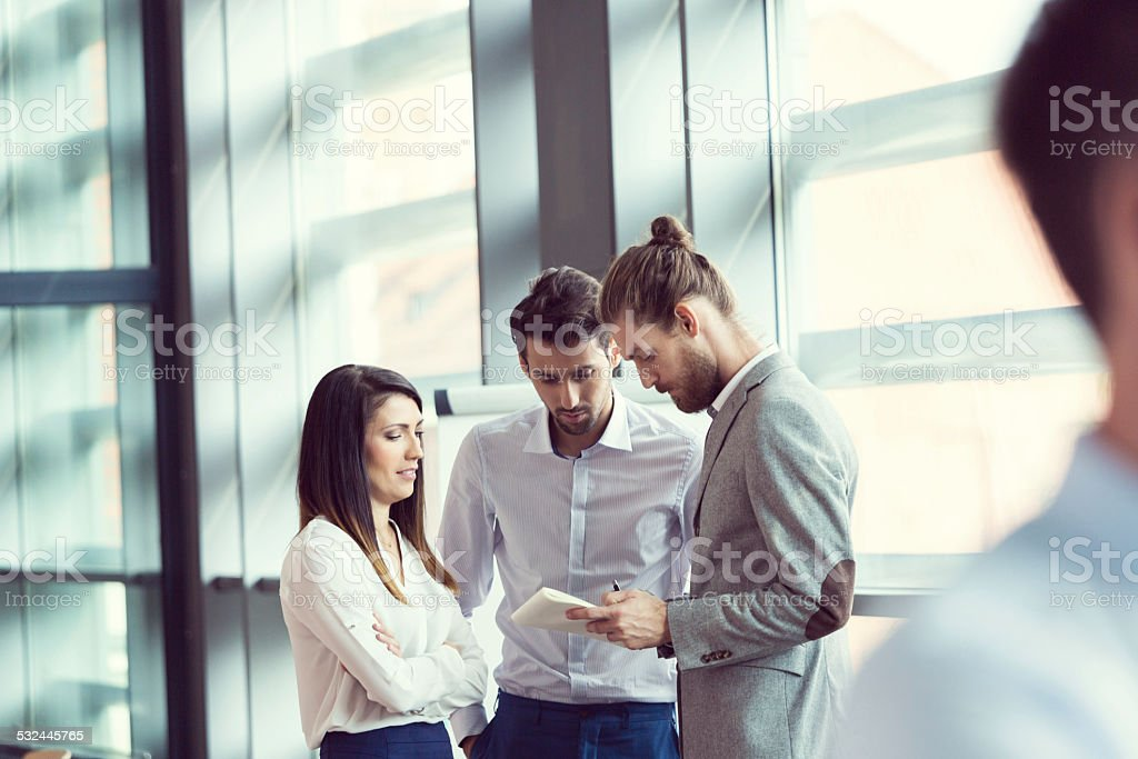 Business people discussing in an office Coworkers talking in an office, discussing a confract. 2015 Stock Photo