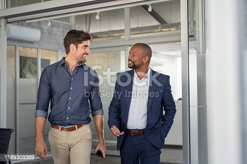 Multiethnic business colleagues walking in office while talking. Two successful business partners in modern office having conversation. Confident young businessman and mature boss discussing on new project.