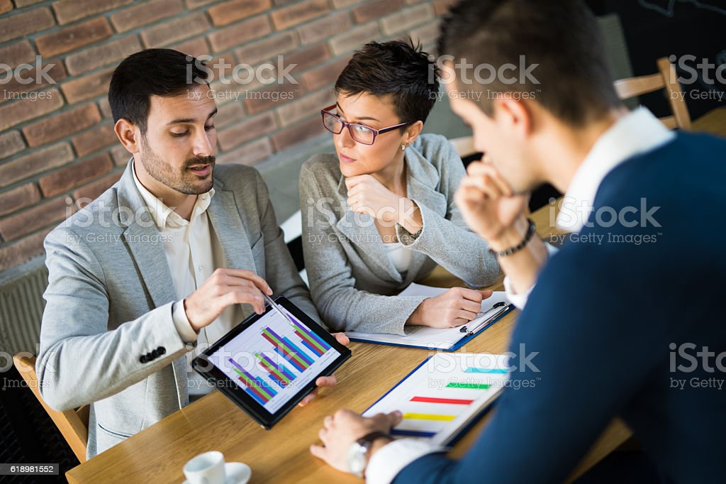 Business people discussing market research statistics during business meeting. stock photo
