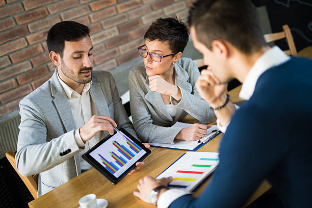 Business people discussing market research statistics during business meeting. Business people discussing market research statistics during business meeting. financial report stock pictures, royalty-free photos & images