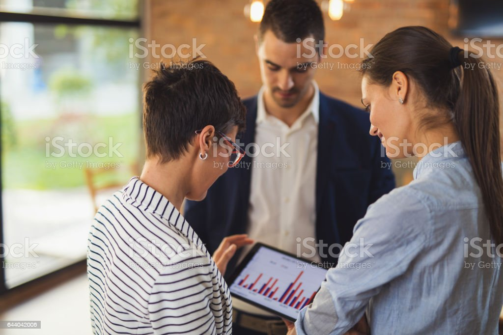 Business people discussing market research statistics during business meeting stock photo