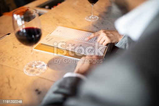 Close-up of two business colleagues sitting at a bar counter and looking at menu card. Couple discussing menu with male partner.