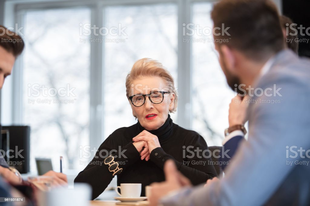 Business people discussing new project in meeting Senior businesswoman talking with colleagues in conference room. Business people discussing new project in the office Active Seniors Stock Photo