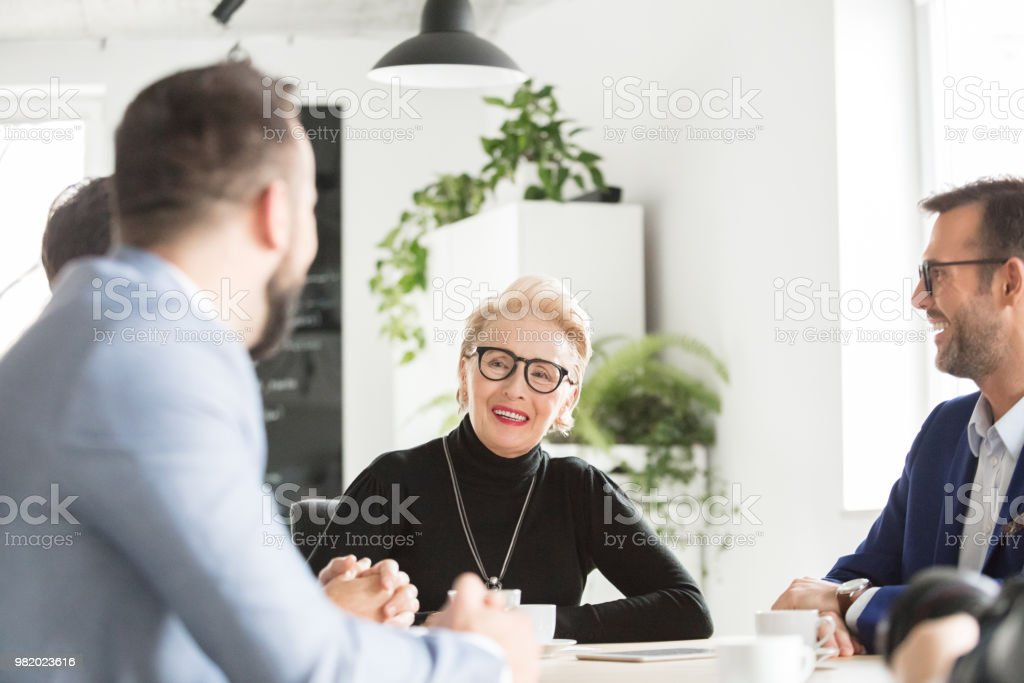 Business people discussing new project Senior businesswoman talking with her team in conference room. Business people discussing new project in the office Active Seniors Stock Photo