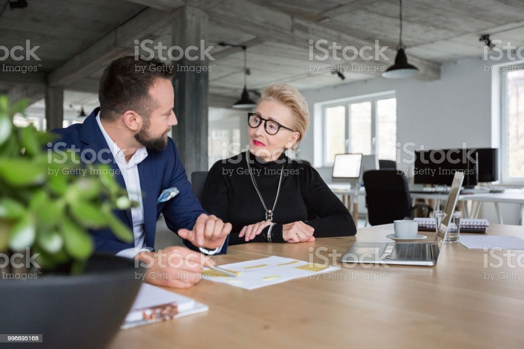 Business people discussing new project Senior businesswoman in discussion with male colleague in office Active Seniors Stock Photo