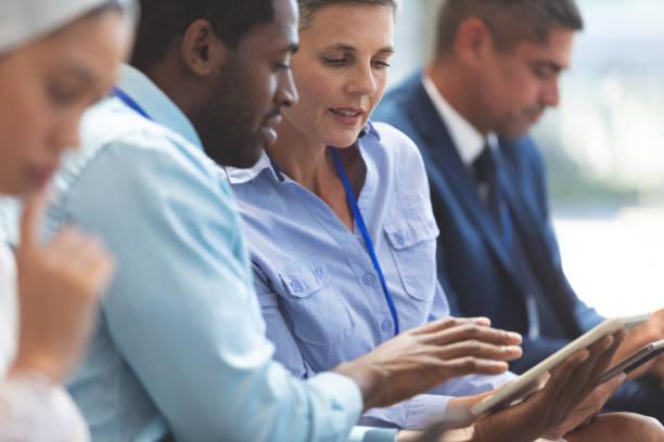 Geschäftsleute diskutieren während des Seminars über digitales Tablet – Foto