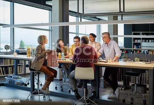 Business people discussing over fabric at conference table. Male and female colleagues are in modern office. They are working in textile factory.