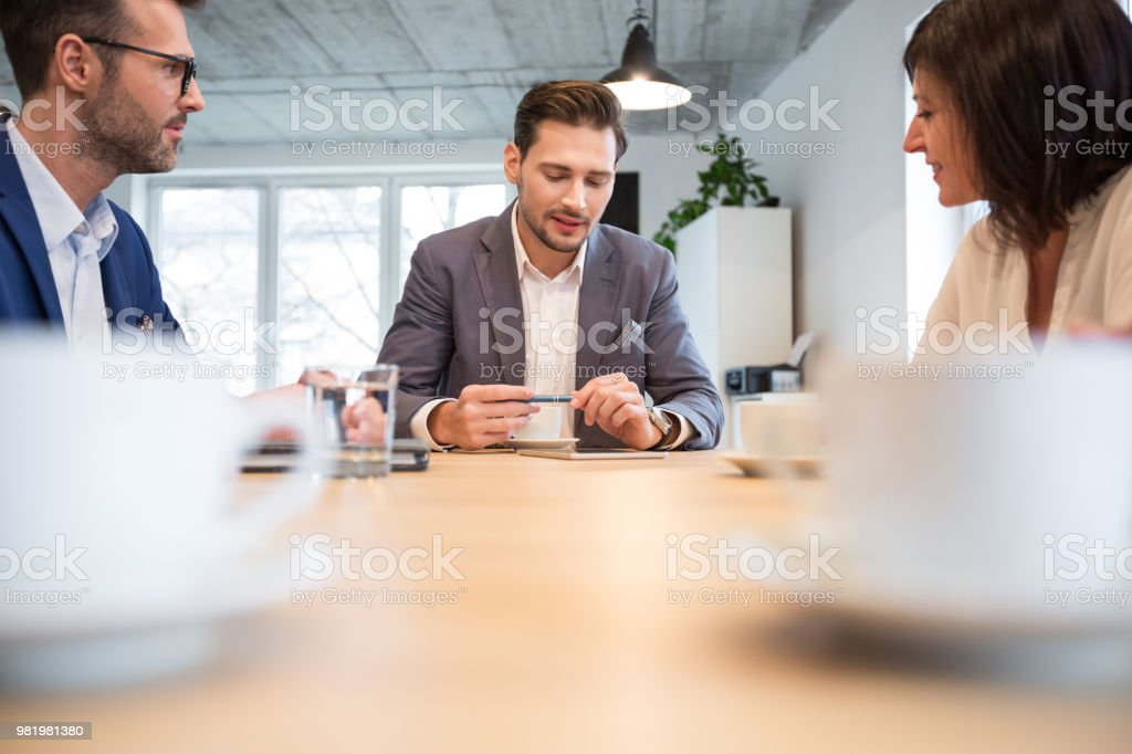Business people discussing over new business project in office Young businessman giving some new ideas about project to his partners in conference room. Business people discussing over new business project in office. Adult Stock Photo