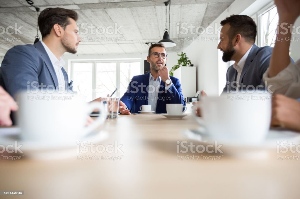 Business people discussing over new project in meeting Mature businessman sharing his ideas with coworkers in boardroom. Business people discussing over new strategies in office meeting. Adult Stock Photo