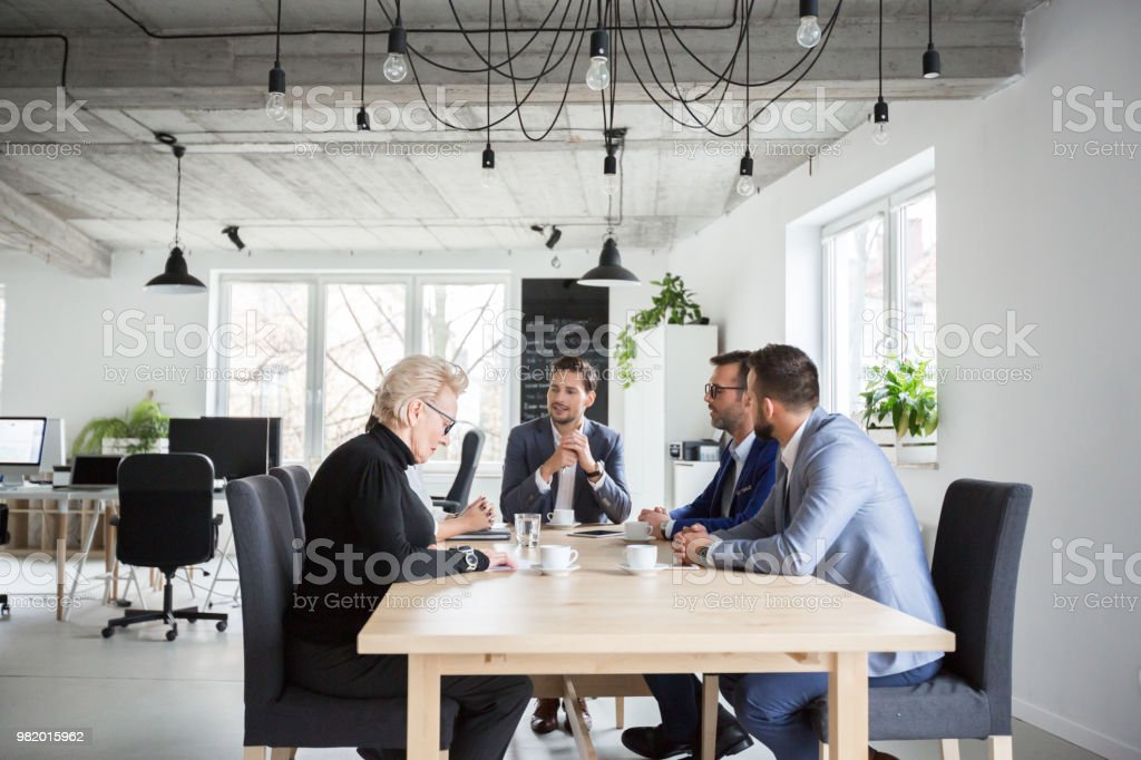 Business people discussing over new project Group of executives discussing during a meeting in office. Businessman and businesswoman sitting at conference table and discussing over new project. Active Seniors Stock Photo