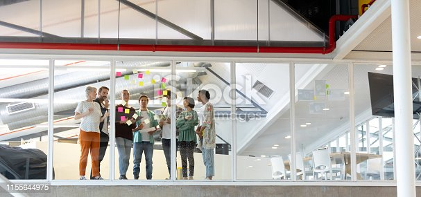 Low angle view of diverse business people discussing over sticky notes in the modern office