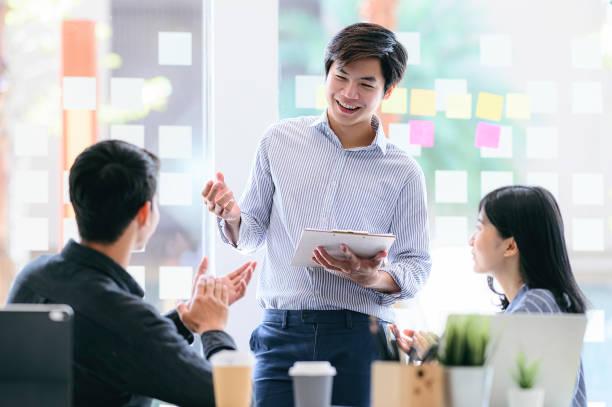 Gente de negocios discutiendo, hablando y sonriendo durante la conferencia en la oficina moderna. - foto de stock