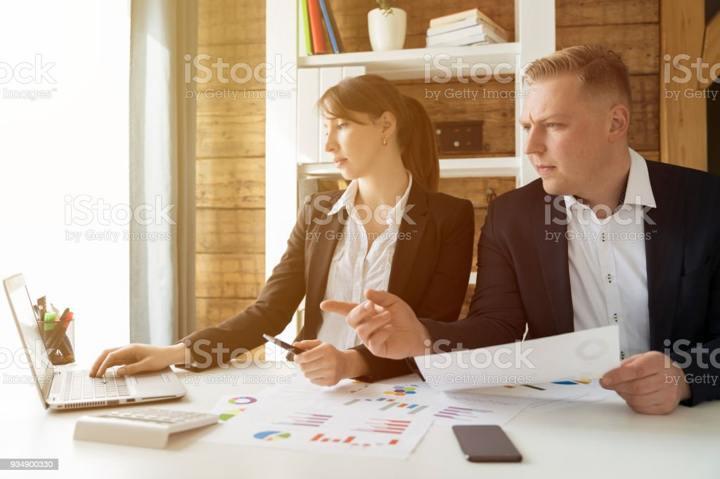 Business people discussing the charts and graphs showing the results of their successful teamwork at office stock photo