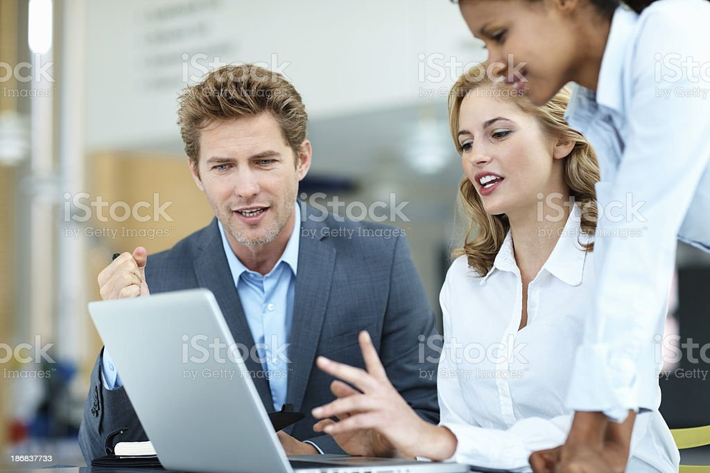 Business people discussing while looking at laptop royalty-free stock photo