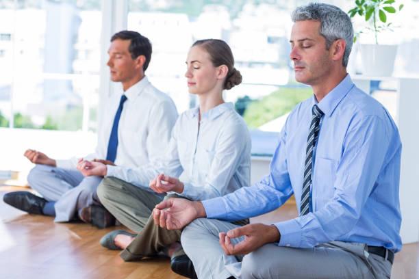 business-leute tun yoga am boden - yoga fürs büro stock-fotos und bilder