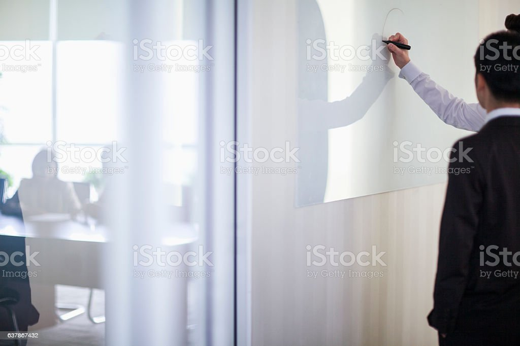 Business people drawing on white board in office stock photo